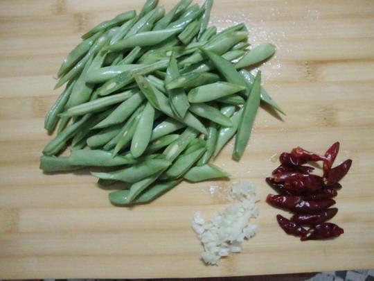 四季豆去除头尾和老筋,洗净切成菱形段,干辣椒洗净切半,蒜去皮洗净