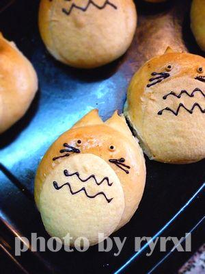 烤箱提前预热180°,放入发酵好的面包坯,175~180°烤制20~25分钟即可。 基本晾凉以后,将巧克力碎装入裱花袋,隔水加热成液体,尖端剪个小口,为龙猫点出眼睛、胡子、花纹即可