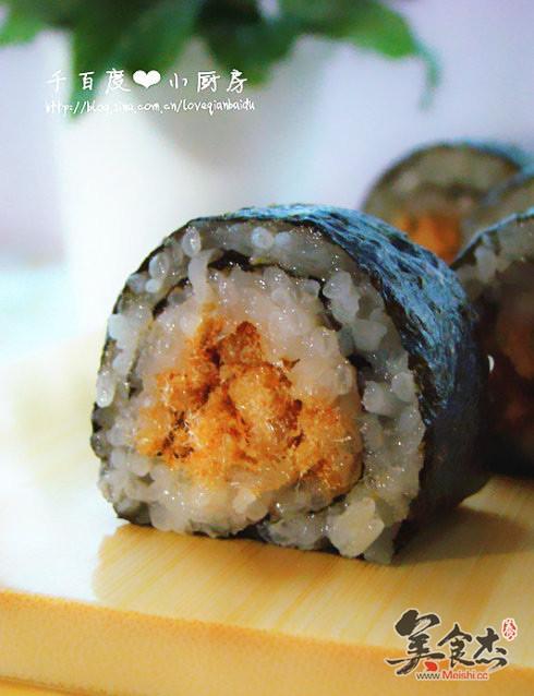 将寿司竹帘扑在桌上,放上寿司紫菜,用寿司铲将米饭扑在紫菜上,摁压